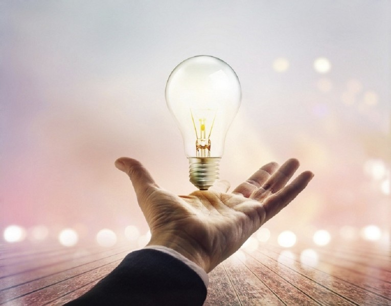 Hands of a businessman reaching to towards light bulb on wooden
